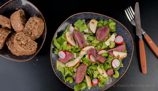 Het gerecht met gebakken ganzenborst met andijvie appelsalade